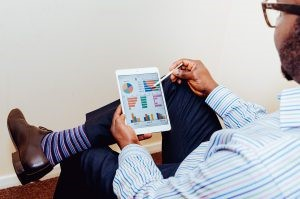 A man analyzing results from surveys on his tablet.